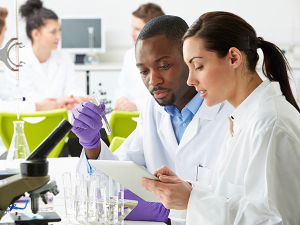 Chemists working in a lab while looking at a tablet and holding a test tube.