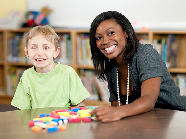 Woman and child smiling with colorful shapes on a table.