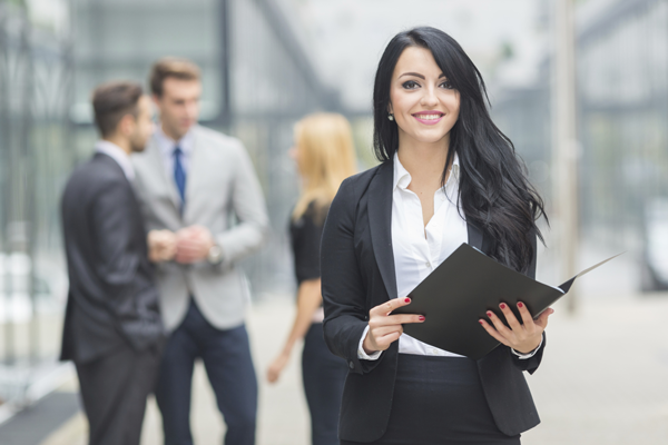 Businesswoman standing holding open folder.