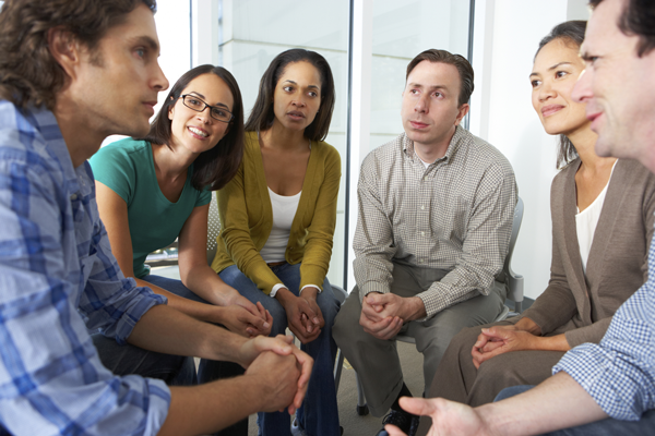 Several people sitting in a circle having a therapy session.